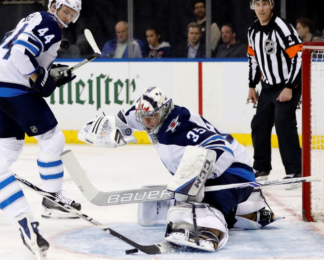 Winnipeg Jets goaltender Steve Mason (35)makes a save with his skate as Winnipeg Jets defenseman Josh Morrissey (44) watches over his shoulder during the second period of an NHL hockey game in New York, Tuesday, March 6, 2018. (AP Photo/Kathy Willens)