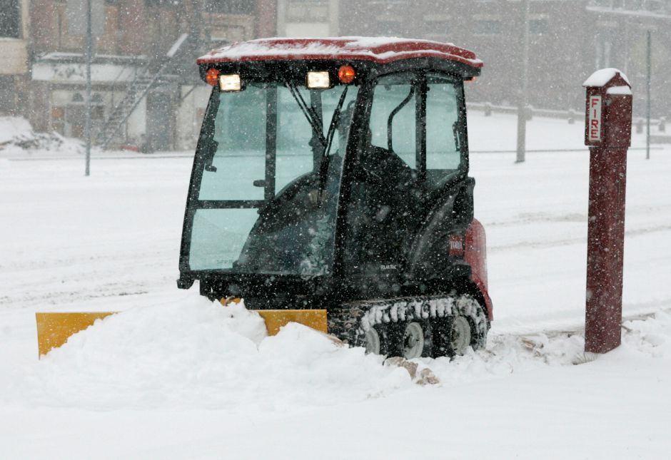 A city employee plows the sidewalks around downtown as the snow falls on Thursday, Dec. 13, 2007.