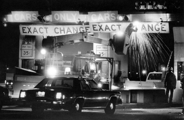 In this Jan. 1, 1986 photo, Connecticut Department of Transportation workers remove signs at the Stratford, Conn., toll plaza on the Connecticut Turnpike as tolls were removed from the state