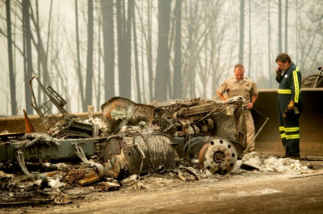 California Capt. Mark Loveless examines a truck scorched by the Delta Fire burning along Interstate 5 in the Shasta-Trinity National Forest, Calif., on Thursday, Sept. 6, 2018. The highway remains closed to traffic in both directions as crews battle the blaze. (AP Photo/Noah Berger)