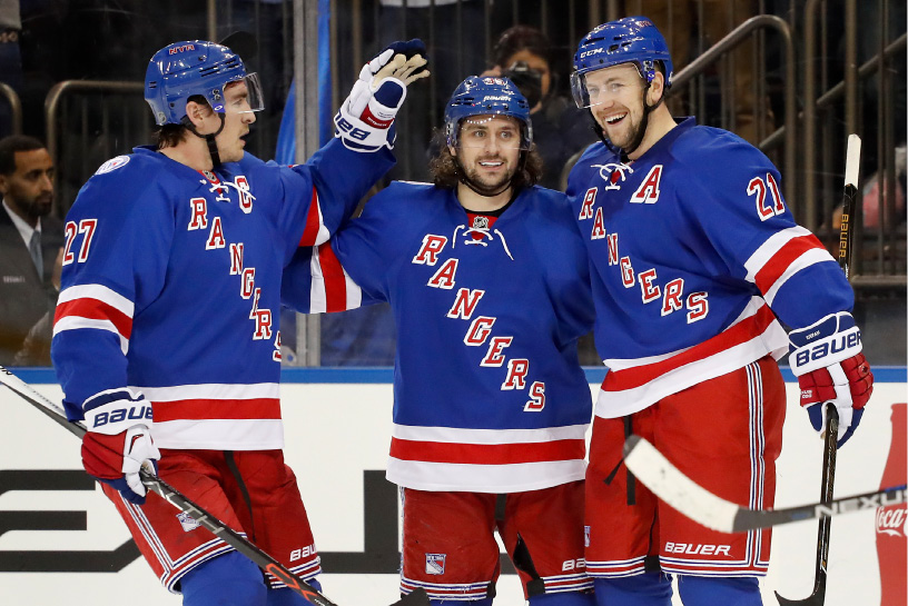Derek Stepan, right, celebrates with Ryan McDonagh, left, and Mats Zuccarello after scoring a goal. | Associated Press