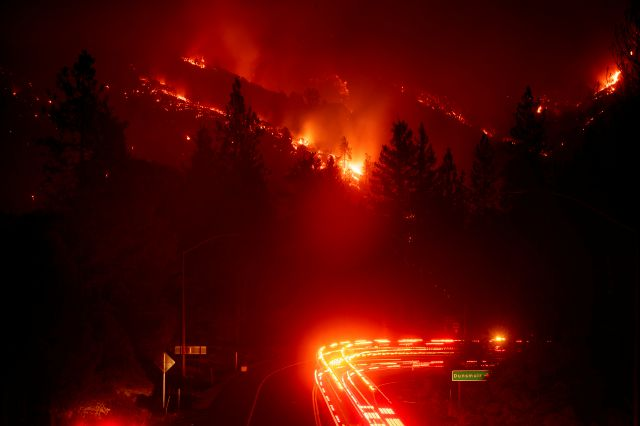 Fire trucks pass the Delta Fire burning in the Shasta-Trinity National Forest, Calif., on Wednesday, Sept. 5, 2018. Parked trucks lined more than two miles of Interstate 5 as both directions remained closed to traffic. (AP Photo/Noah Berger)