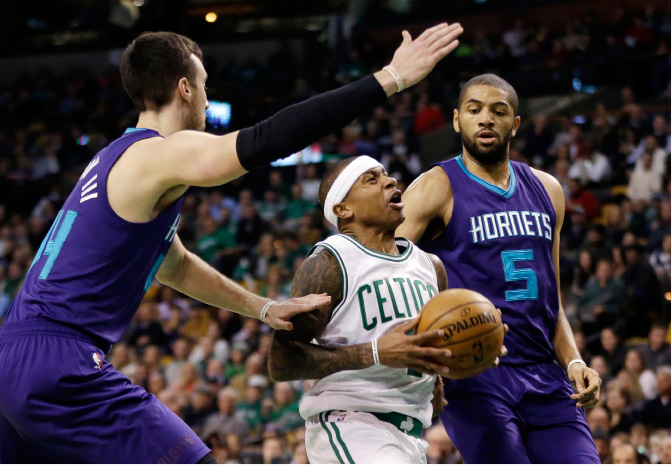 Boston Celtics guard Isaiah Thomas (4) drives between Charlotte Hornets center Frank Kaminsky III (44) and guard Nicolas Batum (5) in the first quarter of an NBA basketball game, Friday, Dec. 16, 2016, in Boston. (AP Photo/Elise Amendola)