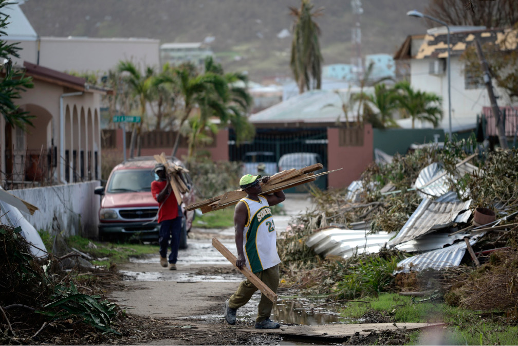 Men remove debris off a road in the Cole Bay community in the aftermath of Hurricane Irma, in St. Martin, Tuesday, Sept. 12, 2017. Hundreds of people across an island shared by Dutch St. Martin and French St. Martin are trying to rebuild the lives they had before it was pummeled by a  Category 5 storm. (AP Photo/Carlos Giusti)