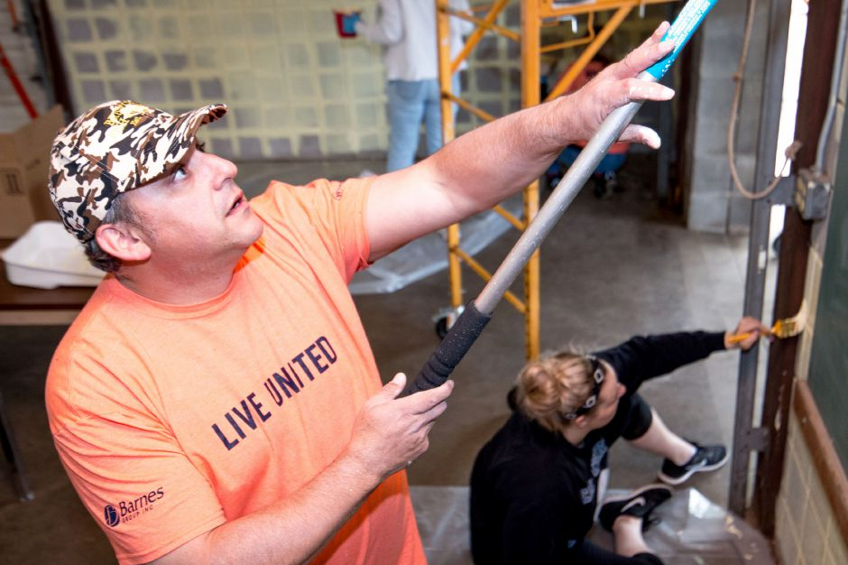 Gregg Karal, president of the Plainville Rotary Club, applies primer to the walls of a building at Norton Park. The club painted the building blue and yellow as part of United Way's Day of Caring on May 18, 2018. | Devin Leith-Yessian/Plainville Citizen