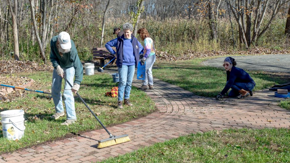 Volunteers clean the pathway to the labyrinth along the Quinnipiac River Linear Trail.  | Devin Leith-Yessian/Record-Journal