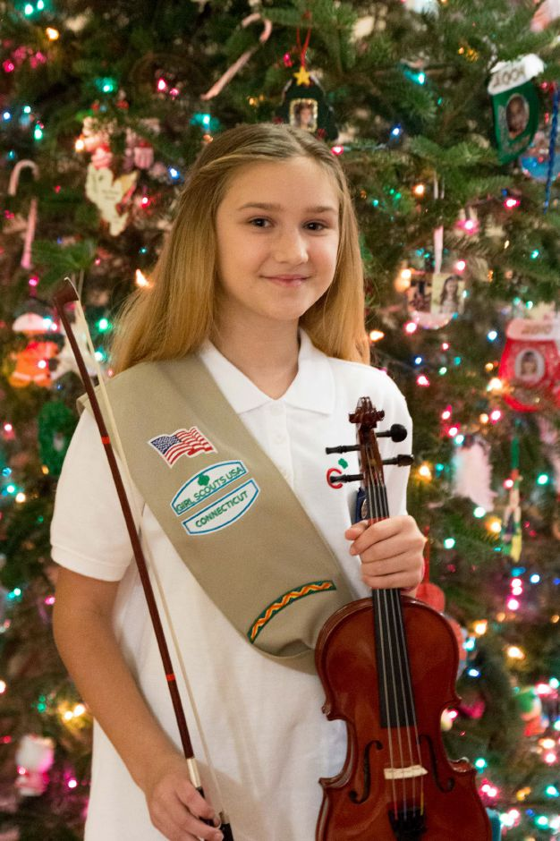 Nicole Kleinhen, 11, of Southington, plays her viola in front of her family Christmas tree. Kleinhen played for the patients at Southington Care Center on Thanksgiving Day after being worried some might go unvisited. | Devin Leith-Yessian/Special to the Record -Journal