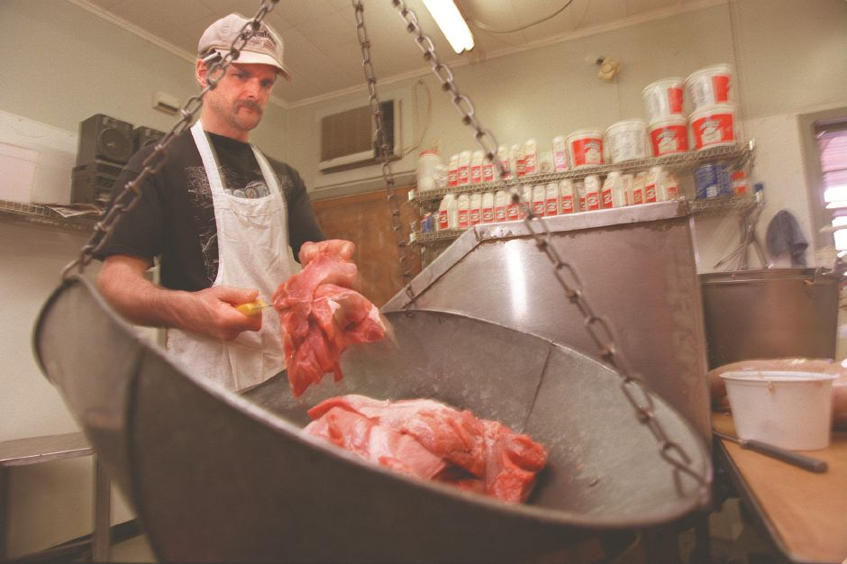 RJ file photo -Ray Czapiga cuts up pork shoulder butt for weighing before it is converted to kielbasa.