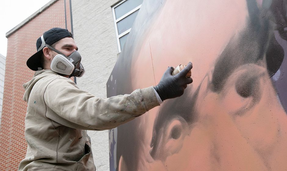 "Global graffiti artist ""ARCY,"" of North Haven, spray paints a portrait of Abraham Lincoln on an 8-foot-by-12-foot canvas outside Lincoln Middle School in Meriden, Mon., Dec. 3, 2018. ARCY is known for large scale art he creates all over the world, and for organizations like Major League Baseball, Disney and the National Parks Service. Dave Zajac, Record-Journal"