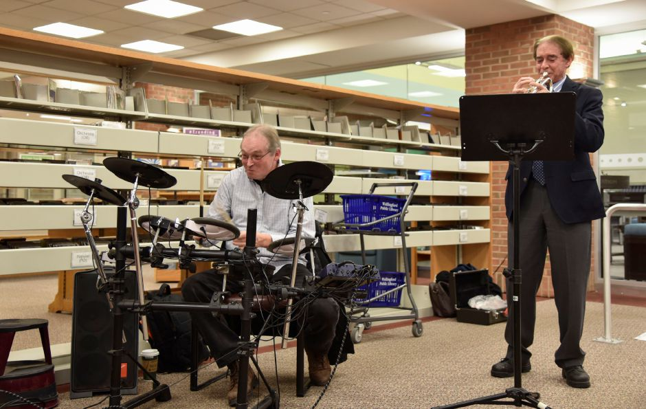 Jim Walton, on drums, and Wallingford Mayor William W. Dickinson, on the trumpet, play a drumroll before revealing the book chosen for the One Book One Wallingford Book program at the library on Wednesday, Jan. 10, 2018. | Bailey Wright, Record-Journal