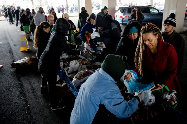 Philabundance volunteers distribute food to furloughed federal workers and their families who are affected by the partial government shutdown, under Interstate 95 in Philadelphia, Wednesday, Jan. 23, 2019. (AP Photo/Matt Rourke)