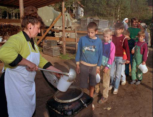 Serbian refugee children wait in a line to get lunch in the village of Tulari at Osren Mountain, Sept.21,1992. Over 100,000 Serb refugees are surrounded by Muslim and Croat forces in this mountain area in northern Bosnia. (AP Photo/Miki Ajder)