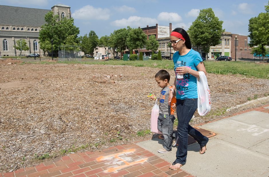Ivette Rivera, of Meriden, and son, Yamil Castro, 5, walk past a lot at 24 Colony St. in Meriden, Wednesday, May 27, 2015. Work on a multi-use building at 24 Colony St., as well as the accompanying parking garage, has stalled in recent weeks because of a misunderstanding between the city housing authority and its development group, and the state Department of Transportation. | Dave Zajac / Record-Journal