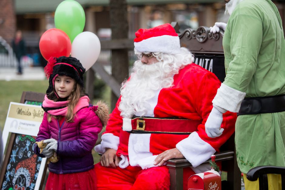 Madison Miller 6 of Meriden stands for a picture with Santa Saturday during the YuleFest Meriden and Holiday Market Place on Colony Street in Meriden November 24, 2018 | Justin Weekes / Special to the Record-Journal