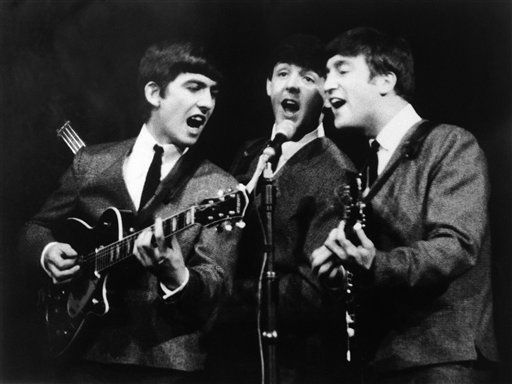 George Harrison, left, Paul McCartney, center and John Lennon, right, three members of the Beatles group during a concert, in London, on Nov. 11, 1963. (AP Photo)