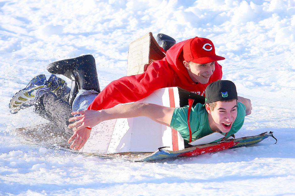 Jordan Pacelle lies on his stomach with only a slab of cardboard between him and the snow. Fellow ski-rental employee of Mt. Southington, Mitch Buonafede, rides on his friends back down Thunderbolt Trail Saturday afternoon during Mt. Southington