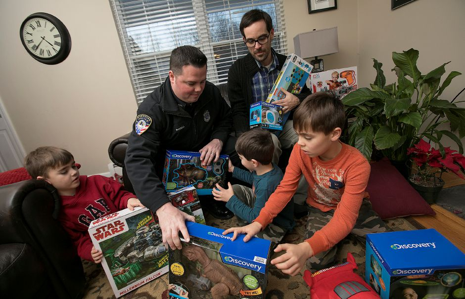 David Maher, of Cheshire, top, looks over donated gifts with his three sons, left to right, Beckett, 6, Alden, 4, and Shepard, 8, along with Cheshire police officer, Jay Bodell at their residence, Wednesday, Jan. 3, 2018. The family