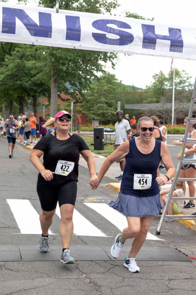 Dorothy Weber, left, and Cindy Paul cross the finish line of the Chips Family Restaurant Road Race on July 21, 2019. The run started on East Street in front of Plainville High School and ended on Robert Holcomb Way. | Devin Leith-Yessian/Plainville Citizen