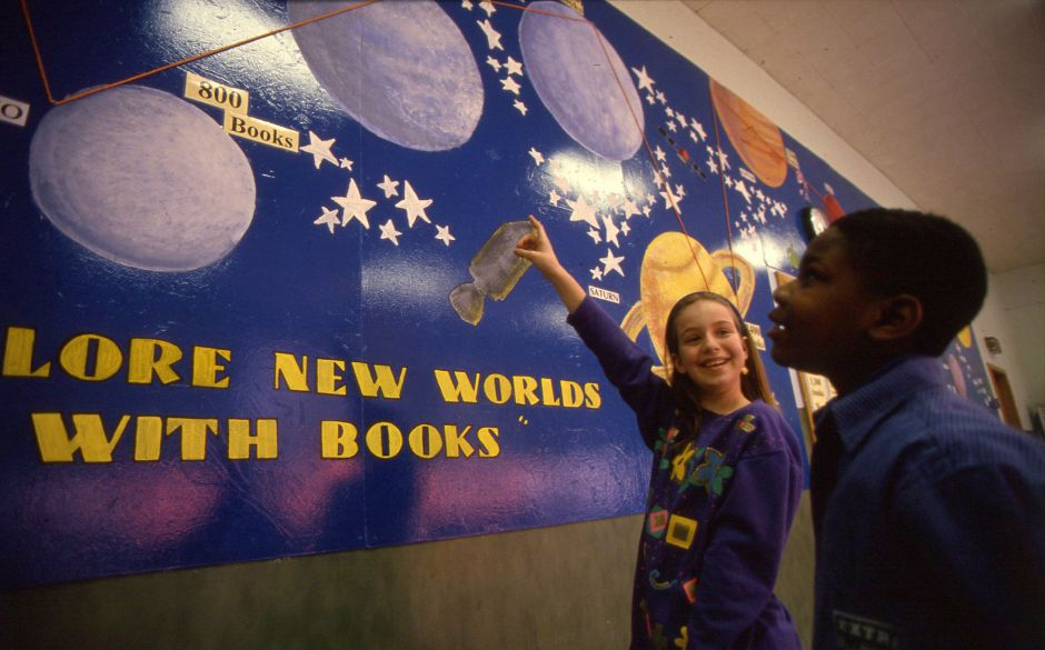 RJ file photo -Marie McManus and Gerald Preston from John Barry School point out the rocket that represents their fourth-grade class. The mural us featured in a program to motivate students to read more books, March 1994.