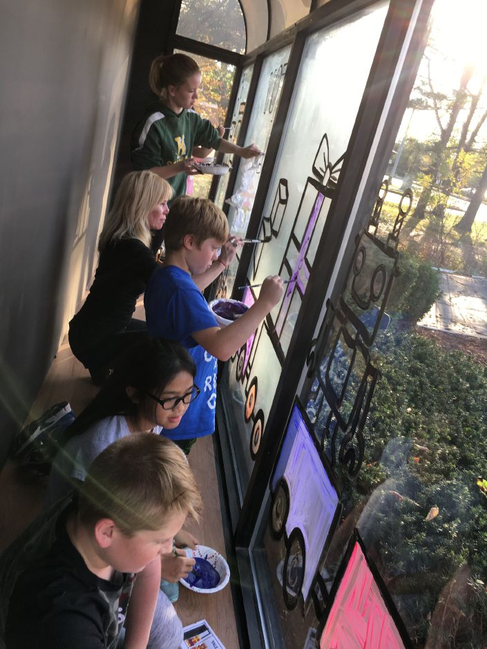 Green Acres Elementary School art teacher Sheri Schwarz, center, and several of her students decorate the window of Now Security Systems on Thursday, Nov. 2, 2017. | Lauren Takores, Record-Journal