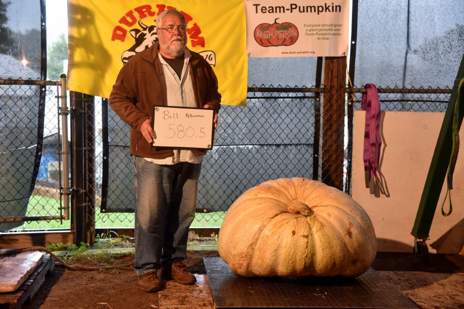 Bill Ackerman stands with his giant pumpkin entry, which weighed 580.5 pounds, on delivery and weigh-in day on Tuesday, Sept. 25, 2018, at the Durham Fairgrounds. The pumpkins will be available for viewing all weekend during the fair. | Bailey Wright, Record-Journal