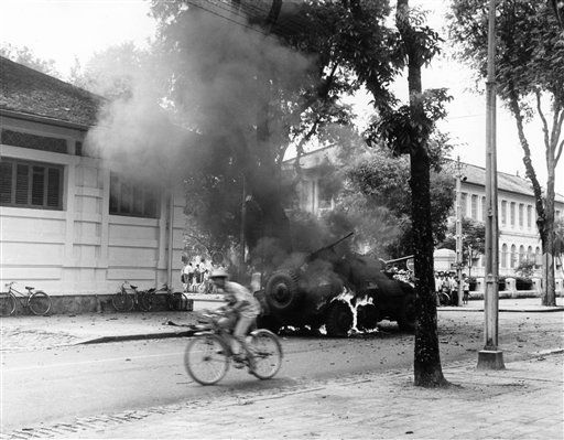 A cyclist rides past a burning armored car in Saigon Street during attack on the presidential palace on Friday, Nov. 14, 1960. Four South Vietnam paratrooper battalions attacked the palace during the uprising. After two days of fighting, President Ngo Dinh Diem's forces were able to stop the revolt. (AP Photo)