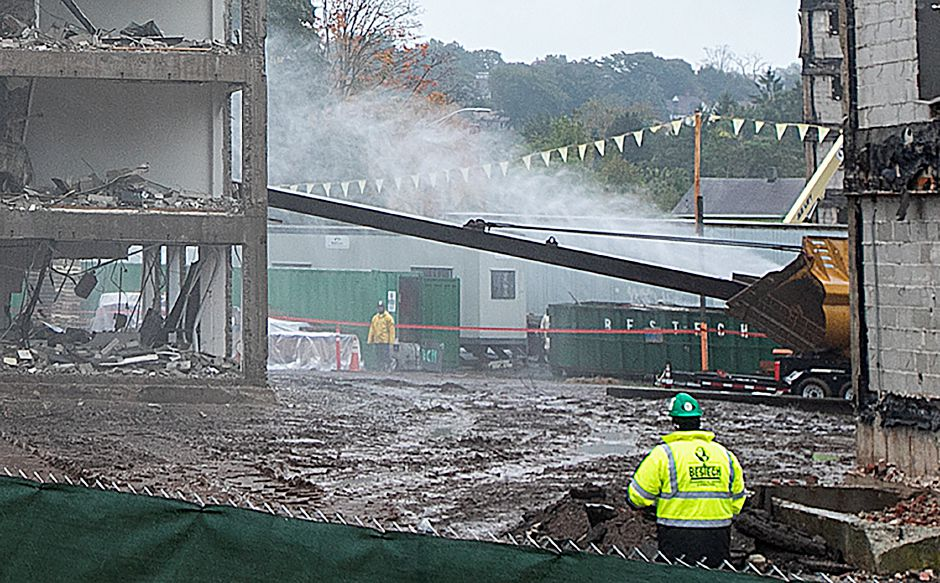 A portion of the former Mills Memorial Apartments at 40 Cedar Street is struck by a steel beam attached to a payloader during a controlled demolition on the site, Monday, Oct. 15, 2018. The payloader strikes at support posts until the building partially collapses. Dave Zajac, Record-Journal