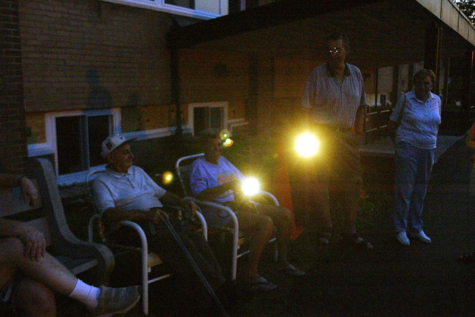 Victoria Towers residents sit outside with their flash lights during the power blackout Thurs., Aug. 14 in Meriden.