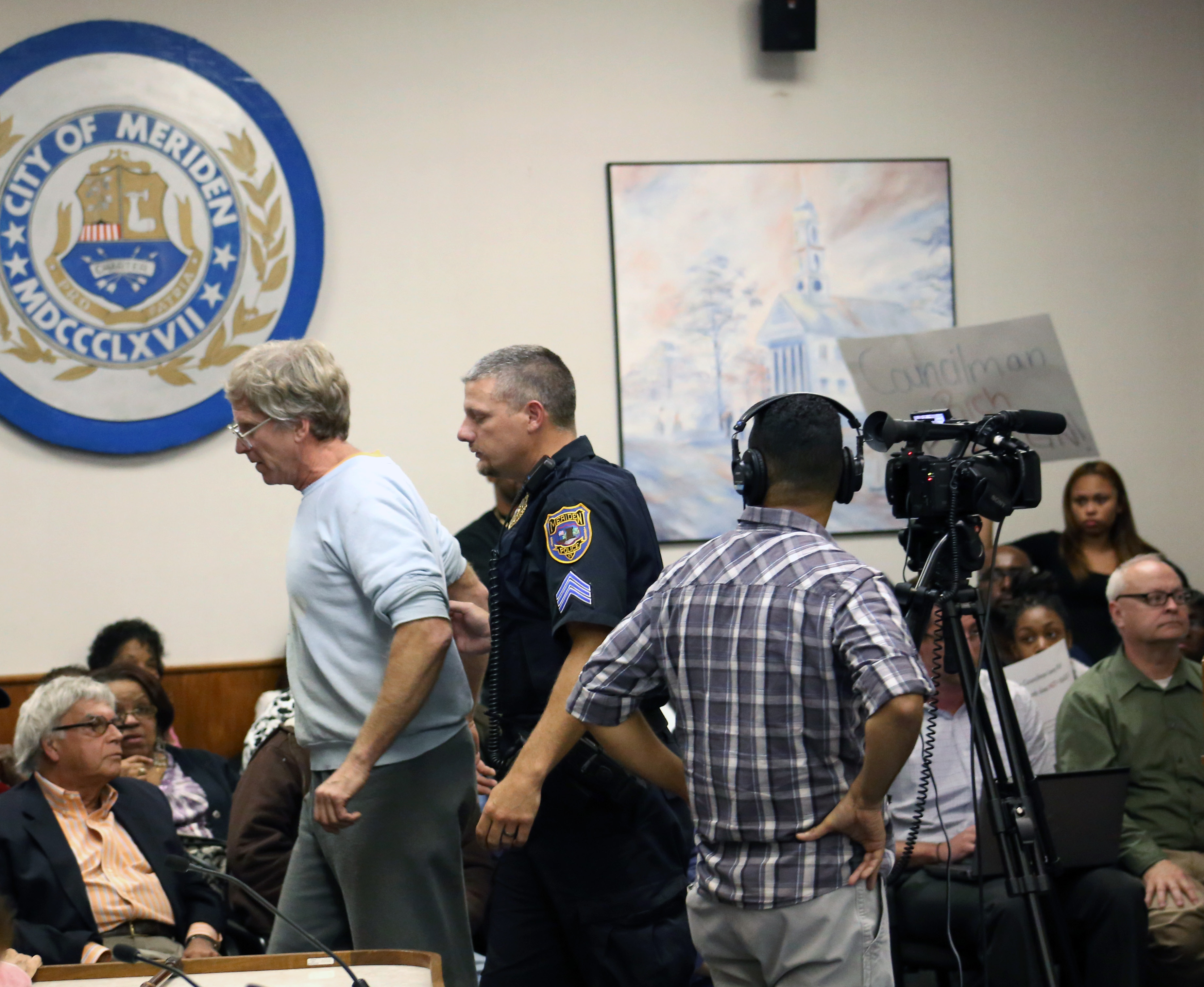 FILE PHOTO -- A Meriden police officer escorts a speaker from a City Council meeting Monday Oct. 6, 2014 after an argument broke out during a public comment session . | Richie Rathsack/Record-Journal