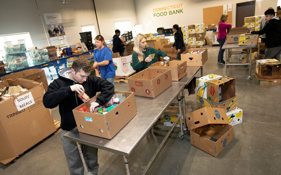 University of Connecticut student Aniello Infante, bottom left,  packs food into  boxes.