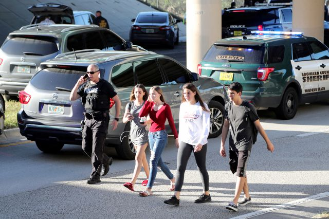 FILE - In this Wednesday, Feb. 14, 2018 file photo, teens, who walked out from the direction of the high school, are escorted by police following a shooting at Marjory Stoneman Douglas High School, in Parkland, Fla. It was the final period of the day at the school and Jonathan Blank was in history class, learning about the Holocaust. Across campus five of his friends, pals since grade school, sat in different classrooms watching the clock, when a former student opened fire at the school, killing more than a dozen people and injuring others Wednesday afternoon. (Amy Beth Bennett/South Florida Sun-Sentinel via AP, File)