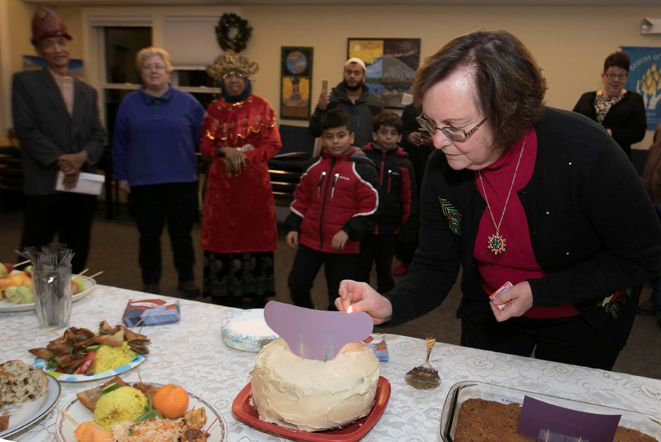 Nancy Burton, coordinator of the Chalice Sanctuary Team, lights the candles of a birthday cake for Sujitno Sajuti during a celebration at the Unitarian Universalist Church on Paddock Avenue in Meriden, Wednesday, Dec. 13, 2017. Sajuti, an undocumented West Hartford resident, has taken up sanctuary at the Unitarian Universalist Church. Dave Zajac, Record-Journal