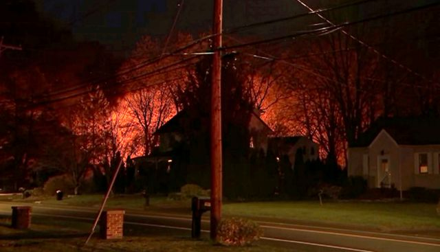 This image provided by WFSB-TV shows a fire behind a house in North Haven, Conn., Wednesday, May 2, 2018. A barn behind a house in Connecticut exploded Wednesday night while police and a SWAT team were negotiating with a man who had taken his wife hostage, leaving at least six officers injured, state police and a town official said. (WFSB-TV via AP)