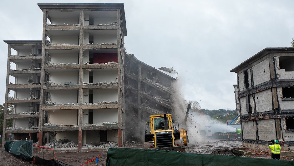 A portion of the former Mills Memorial Apartments at 40 Cedar Street is collapsed by way of a payloader with a steel beam attachment, Monday, Oct. 15, 2018. The payloder strikes at support posts until the building partially collapses. Dave Zajac, Record-Journal