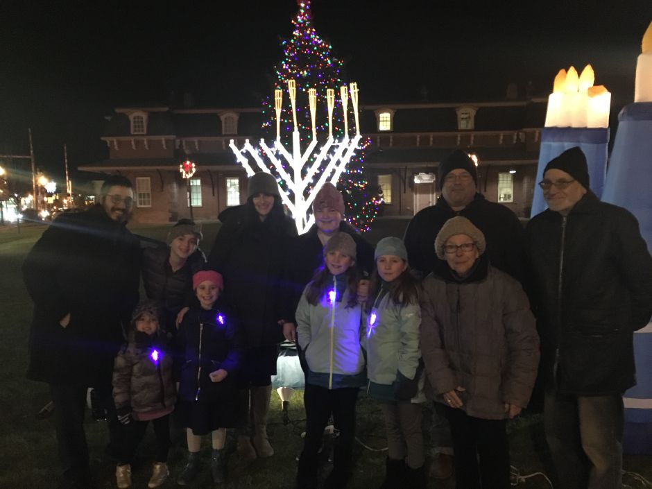 Rabbi Baruch Kaplan (left) and family in front of the menorah prior to the 14th annual public lighting at Wallingford Railroad Green.