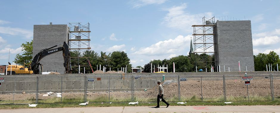 A man walks by the Meriden Commons under construction at the corner of State Street and Mill Street in Meriden, Monday, July 3, 2017. | Dave Zajac, Record-Journal