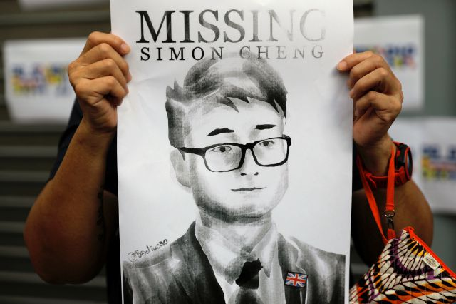 FILE - In this Aug. 21, 2019, file photo, a supporter holds a poster outside of the British Consulate in Hong Kong during a rally in support of an employee of the consulate who was detained while returning from a trip to China. A former employee of the British Consulate in Hong Kong says he was detained and tortured by Chinese secret police trying to extract information about massive anti-government protests in the territory. (AP Photo/Vincent Yu, File)