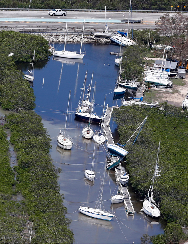 Boats, some partially submerged, float in a canal in the wake of Hurricane Irma, Monday, Sept. 11, 2017, in Key Largo, Fla. (AP Photo/Wilfredo Lee)