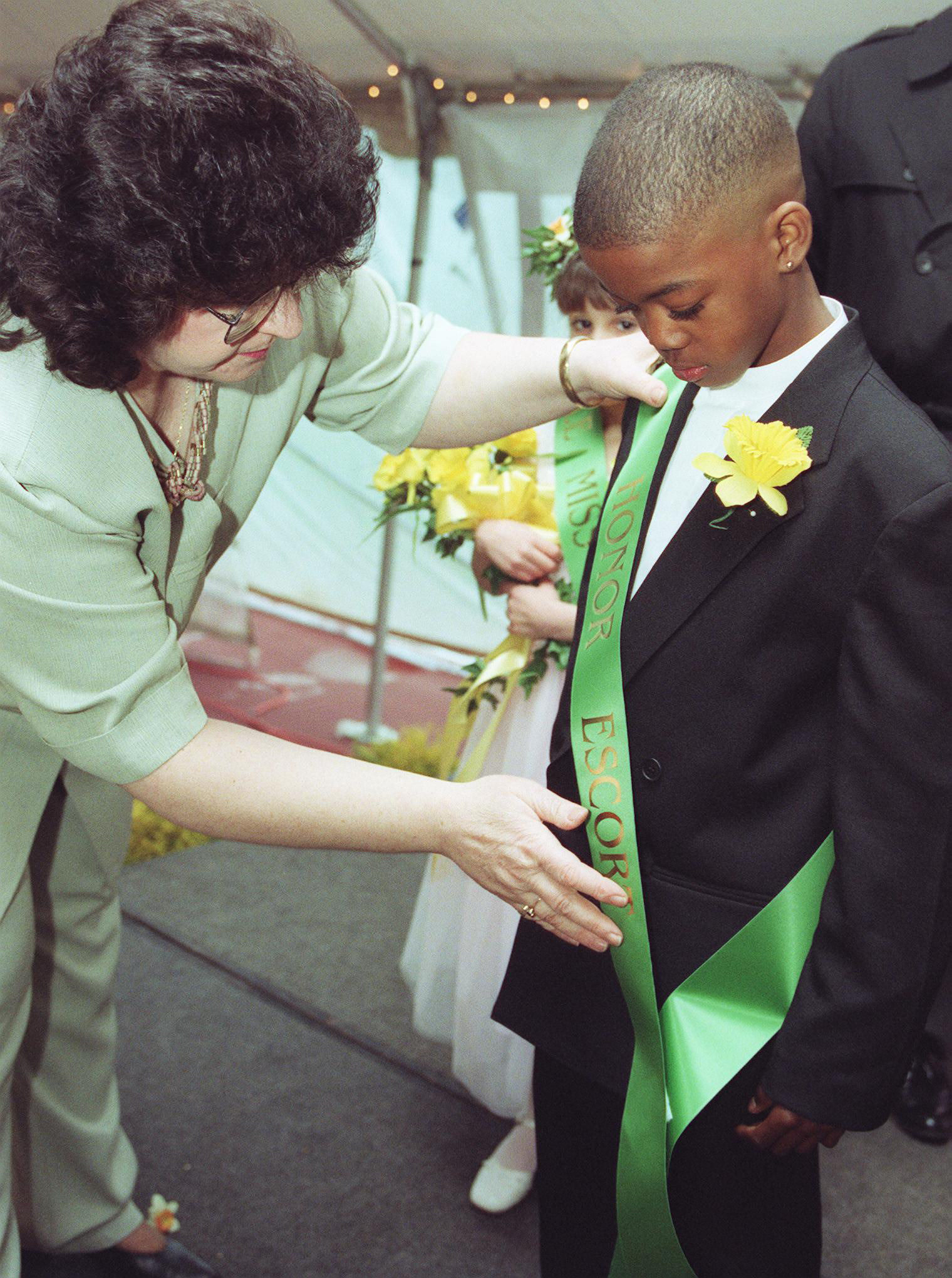 Doreen Roddy puts the sash on Tyler Hoffler, of Casimir Pulaski School, who was chosen as the honor escort for Little Miss Daffodil Wed., April 26 at Hubbard Park.