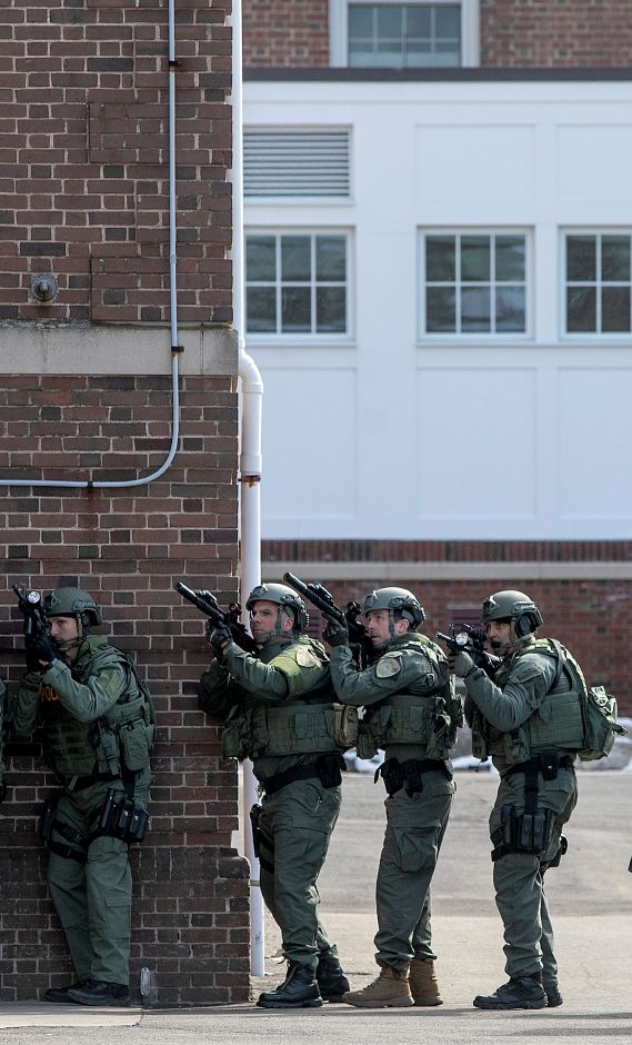At left, unit members focus on second-floor windows on Thursday while entering the dining hall during a training exercise at Choate Rosemary Hall in Wallingford.