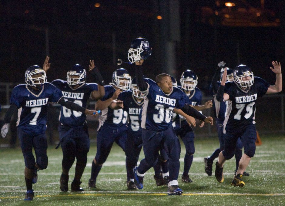 Meriden Raiders led by #30 Handy Ellison, center, celebrate defeating Newtown in the American Youth Football State Finals 8th grade division at Falcon Field in Meriden November 14, 2010. (Dave Zajac/Record-Journal)