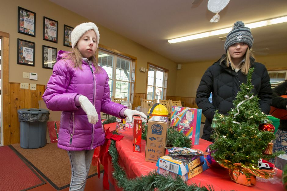 Caitlin Taylor 17 left and Emily Piscoglio 17 organize the donation table Saturday during Santa at Sloper hosted by the Mill Foundation at the YMCA