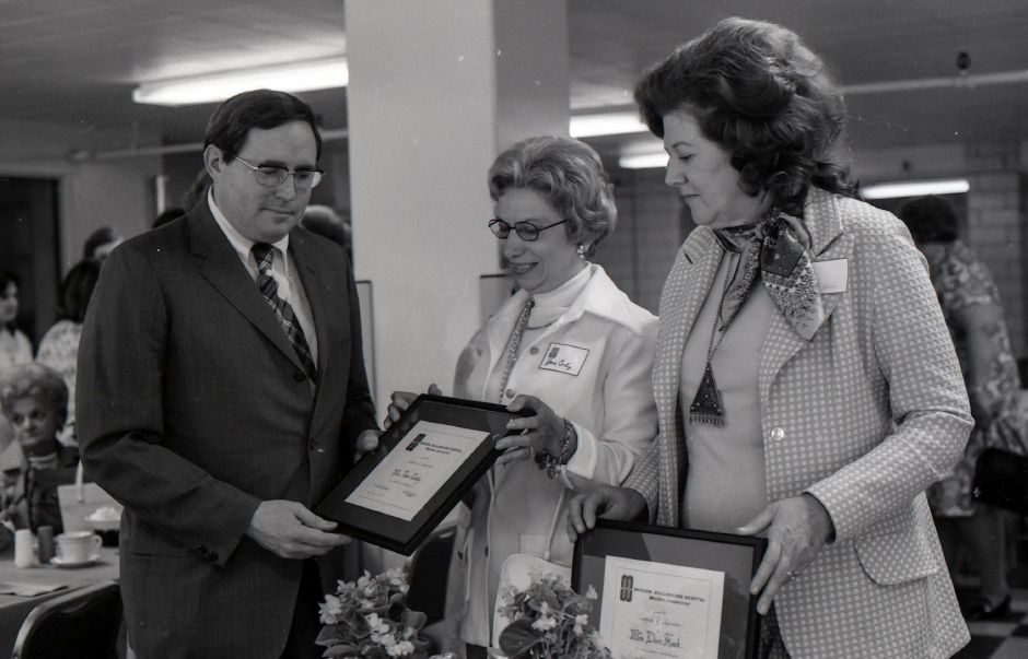 Mrs. Jane Corby, center, and Mrs. Dory Koch, right, an employee of the Meriden-Wallingford Hospital who devotes her artistic talents, were the recipients of special certificates of appreciation, June 1975. Administrator Jack McIntyre, left, presented the awards.