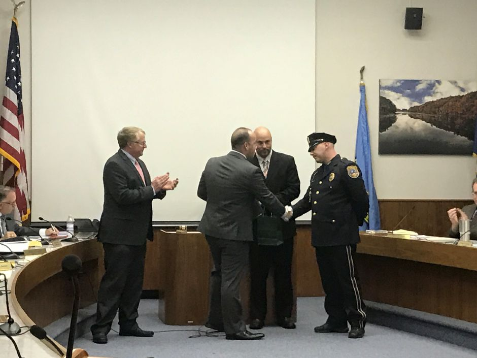 Police Det. Kevin Ieraci, right, receives the Spirit of Meriden award for giving gifts to children at a homeless shelter on Christmas Eve. Also pictured: Police Chief Jeffry Cossette, Mayor Kevin Scarpati and Deputy Mayor Michael Cardona. | Leigh Tauss, Record-Journal