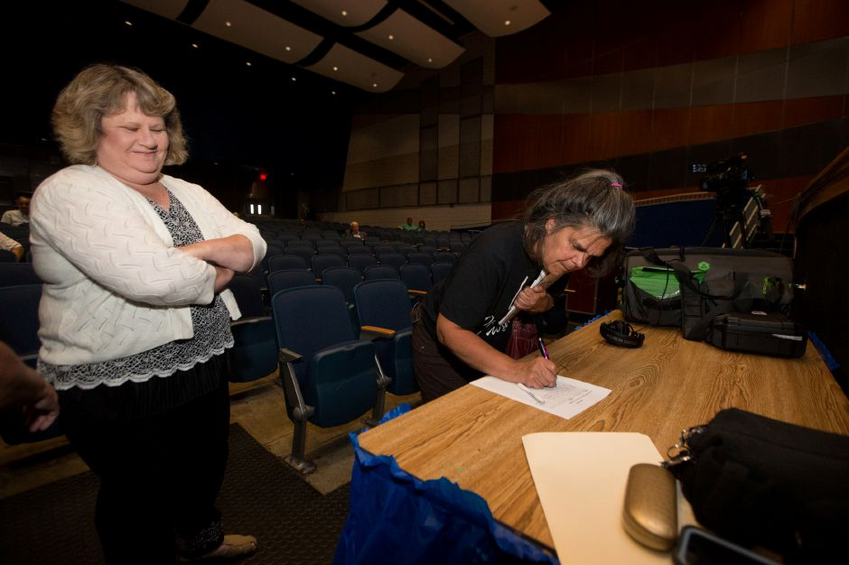 Meriden residents Carol Murphy right and Holly Wills sign up to speak Thursday during a public hearing with the Meriden Finance Committee to speak about the tax increase at Lincoln Middle School in Meriden August 9, 2018 | Justin Weekes / Special to the Record-Journal