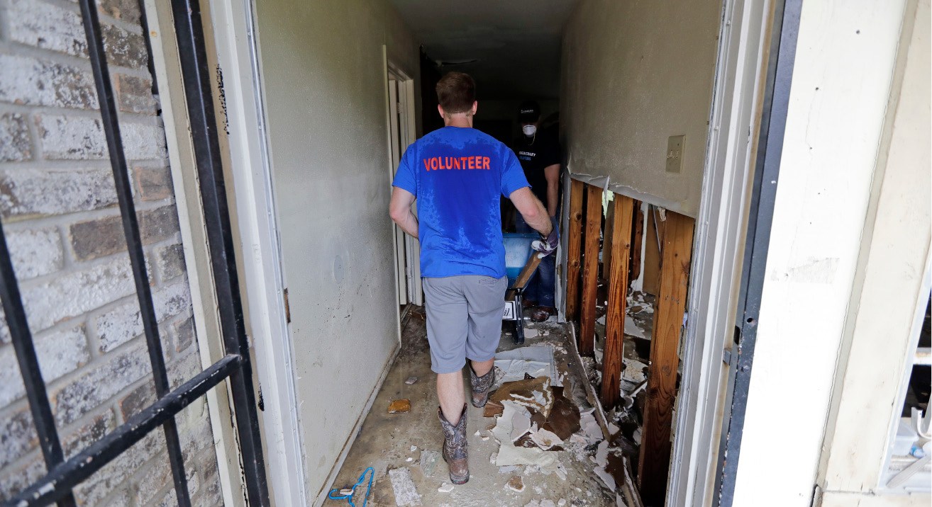Volunteer Trent Hartman helps clean up the home of Julia Lluvia, which was destroyed by floodwaters, in the aftermath of Hurricane Harvey Monday, Sept. 4, 2017, in Houston. (AP Photo/David J. Phillip)