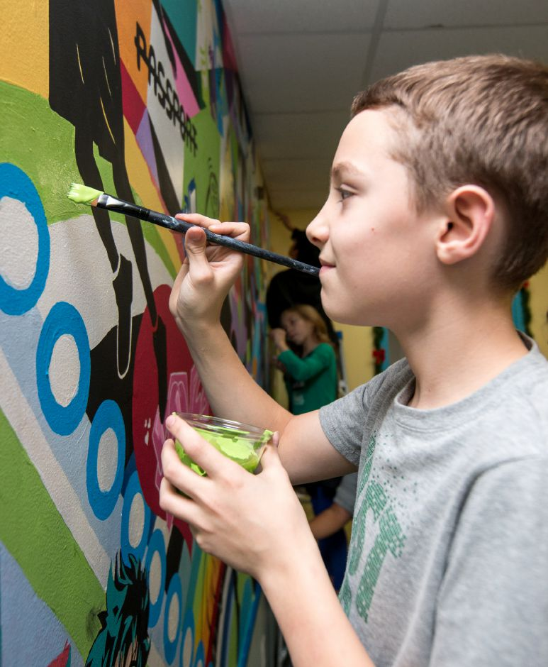 Taylor Boss, 11, adds his own touch to the mural.