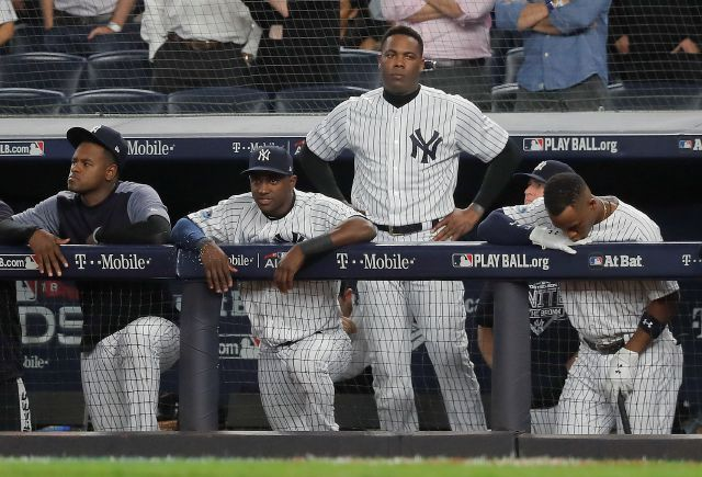 The New York Yankees watch from the dugout during the ninth inning of Game 4 of baseball