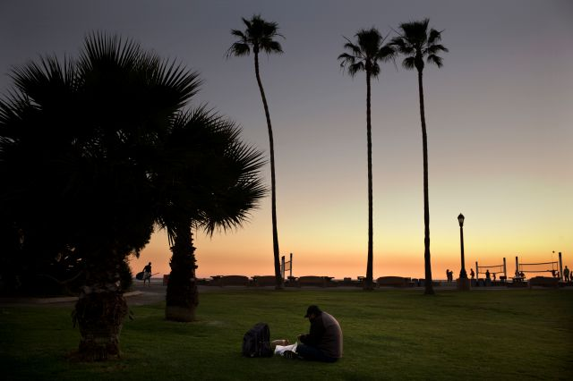 Sitting on the lawn at Doheny State Beach, Gholamreza Hagihgih, a 59-year-old Iranian immigrant who has been homeless for 20 years, eats his meal provided by a nonprofit organization Thursday, Dec. 21, 2017, in Dana Point, Calif. Goodhearted neighbors heartbroken over the rising number of homeless in their communities are dishing out hot meals, providing mobile showers and handing out sandwiches to those in need, hoping they can make a difference. (AP Photo/Jae C. Hong)