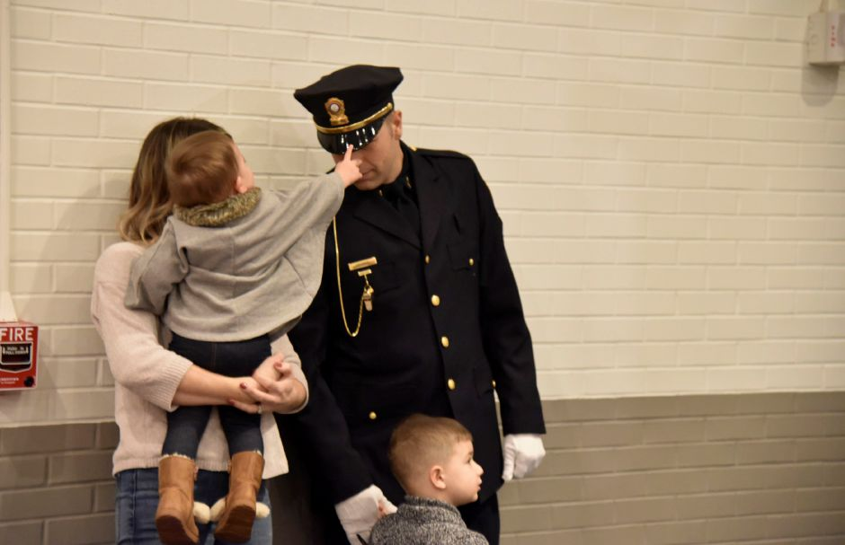 Giuliana Gaspar, 1, touches the uniform of her father, John Gaspar, as they wait for his swearing-in to the position of sergeant Tuesday, Jan. 15 at North Haven Middle School.